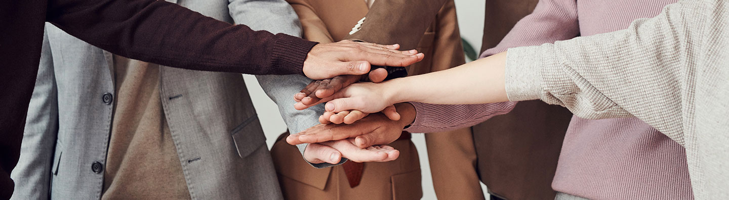 A group of people touching hands.